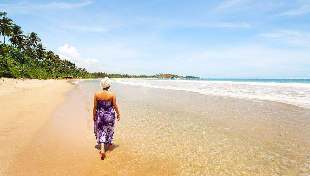 Frau zu Fuß am Strand nach Ayurveda kur in Sri Lanka